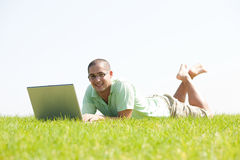 A young men lying on the in the park with laptop. A young men lying on the grass in the park using a laptop stock images