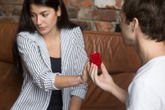 Unhappy girl refusing to marriage proposal of boyfriend. Young men making marriage proposal to dissatisfied women presenting wedding ring, girl refusing to marry stock image
