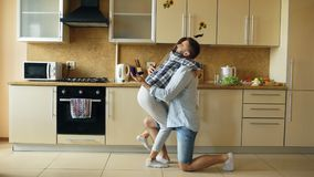 Young man making proposal to his girlfriend in the kitchen at home Royalty Free Stock Photos