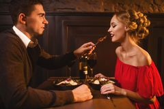 Man meals elegant woman in red dress in restaurant Royalty Free Stock Photo