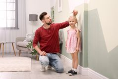 Young man measuring his daughter`s height. Young men measuring his daughter`s height at home royalty free stock photography