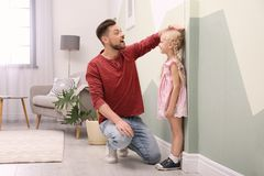 Young man measuring his daughter`s height. Young men measuring his daughter`s height at home stock image