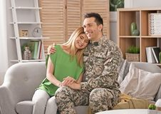 Young man in military uniform with his wife on sofa Royalty Free Stock Photography