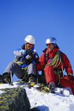 Young men mountain climbing on snowy peak royalty free stock images