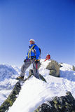 Young men mountain climbing on snowy peak Stock Images