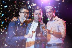 Young men at night party. Joyful young Asian people drinking champagne under falling confetti at night party royalty free stock photography