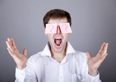 Young men with notes on eyes. Royalty Free Stock Photo