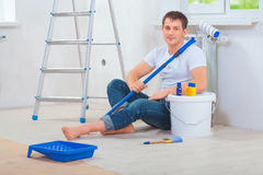 A young men painter sitting on floor holding paintroller and loo. A young man painter sitting on floor holding paintroller and looking  at camera Stock Photos