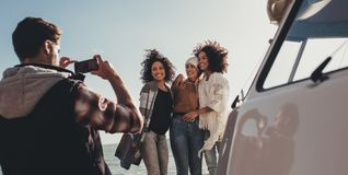 Group of young people on road trip taking pictures. Young men photographing of female friends on seaside. Group of young people on road trip taking pictures Royalty Free Stock Photography