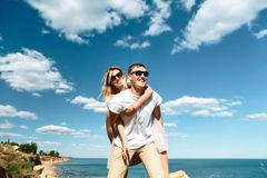 Young man piggybacking his happy girlfriend with raised hand in glasses on the rock in the sea near the beach with big cliffs, Bla stock photography