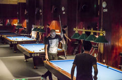 Young men play billiards royalty free stock photos