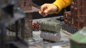 Young men play table miniature military role-playing game stock footage