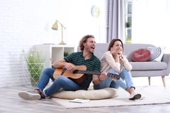 Young man playing acoustic guitar badly for displeased girlfriend in living room. Young men playing acoustic guitar badly for displeased girlfriend in living royalty free stock photo