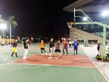 Young men are playing basketball, at night Royalty Free Stock Images