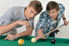 Young men playing billiards Stock Photo