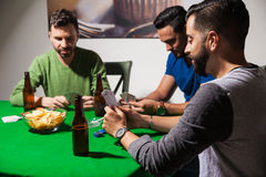 Young men playing cards at night. Group of three male friends drinking beer and eating snacks while playing some poker at night Royalty Free Stock Photography
