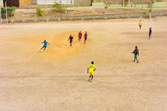 Young men playing a casual game of soccer on a dry field in the tropics Stock Photos