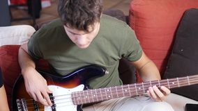 Young men playing electric guitars. Two casual guys posing on sofa and playing electric guitar and bass in band stock video footage