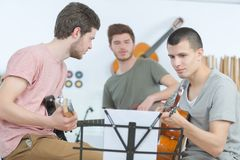 Young men playing guitar and composing song. Young men playing guitar and composing a song Royalty Free Stock Photos