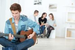 Young man playing guitar. Young men playing a guitar stock image