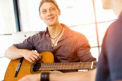 Young man playing the guitar in office Stock Photos