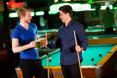 Young men playing pool and drinking beer Royalty Free Stock Photography