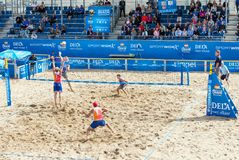 Young men playing professional beach volleyball match in outdoor arena. The Hague, Netherlands - August 26, 2018: Young men playing professional beach volleyball royalty free stock images
