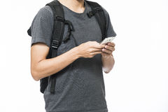 Young men playing smart phone standing against white background Royalty Free Stock Images