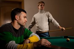Young men playing snooker. Concentrating on game, blond guy holding cue Stock Photo