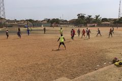 Young men playing soccer in a dirt field in the city of Bissau, in Guinea-Bissau. Bissau, Republic of Guinea-Bissau - January 28, 2018: Young men playing soccer Royalty Free Stock Images