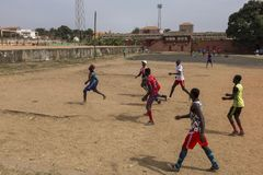 Young men playing soccer in a dirt field in the city of Bissau, in Guinea-Bissau. Bissau, Republic of Guinea-Bissau - January 28, 2018: Young men playing soccer Stock Images