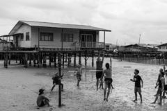 Young Men Playing Volleyball Boys Low Tide Residential Poor Village Poverty Stricken royalty free stock image