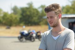Young man posing with motorbike in background Stock Image