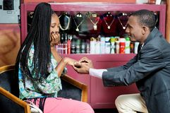 Young man puts a ring on the finger of his companion. Young men puts a ring on the finger of his companion, astonished she manifests her joy royalty free stock photos