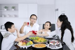 Young man raises glass with his family. Young men raising a glass with his family while having lunch together in the kitchen stock image