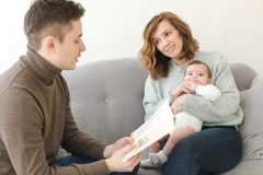 Father reading book to child and mother. Young men reading book for child and mother on couch at home Royalty Free Stock Photography