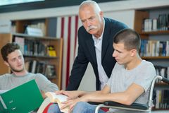 Young man reading book while teacher observing. Young men reading a book while the teacher is observing Stock Photo