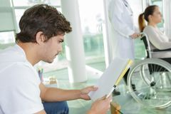 Young man reading while waiting in hospital lobb. Young men reading while waiting in the hospital lobb royalty free stock images