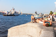 Young men relaxing on the waterfront on the background of warshi Royalty Free Stock Photo