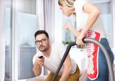 Woman vacuuming while man watching tv Stock Photo