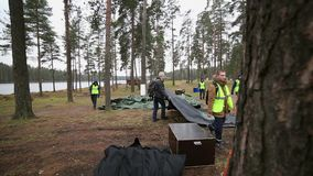 Young men in rescue uniform to establish tent in forest, lake. Emercom camping. Several men in rescue uniform to establish tent in forest, lake. Emercom teaching stock footage