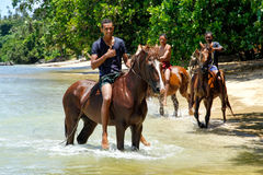 Young men riding horses on the beach on Taveuni Island, Fiji Stock Images