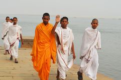 Young men by the river. Young men dressed in a traditional costume of Buddhist priests walk along the river and wave to tourists who photograph them royalty free stock photography