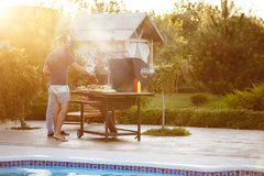 Young men roasting barbecue on grill in cottage countryside. Stock Images