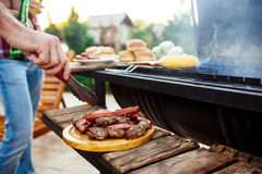 Young men roasting barbecue on grill in cottage countryside. Royalty Free Stock Photos