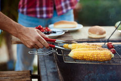 Young men roasting barbecue on grill in cottage countryside. Stock Image