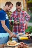Young men roasting barbecue on grill in cottage countryside. Stock Photo
