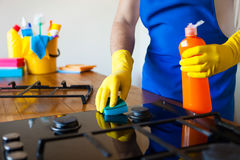 Young Men in rubber protective cleaning and polish cooker. Black. Shiny surface of kitchen top, hands, detergent. Set cleaning concept Royalty Free Stock Photo