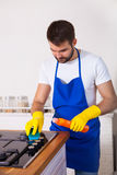 Young Men in rubber protective cleaning and polish cooker. Black Stock Photography