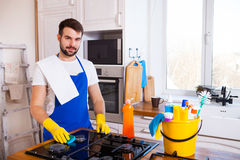 Young Men in rubber protective cleaning and polish cooker. Black Stock Photos